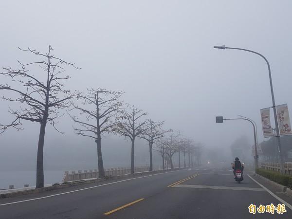 金門縣一早大霧罩頂,車輛行進都打開大燈,宛如身陷「霧都」(記者吳正庭攝)