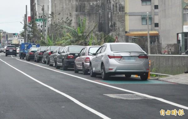 後龍鎮公所在中山路北側路肩,劃設有綠色方格,部分還有「大人牽孩童」圖案,讓家長以為是通學步道,卻遭車輛占用,公所解釋為非通學步道範圍。(記者彭健禮攝)