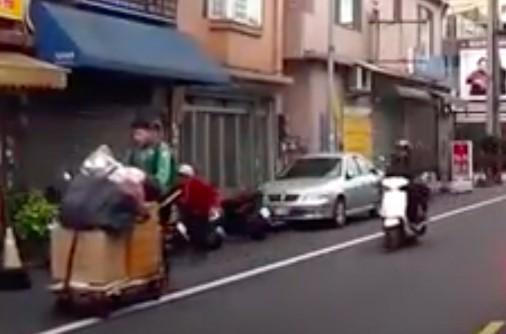 黃柏翔主動幫嬌小的老婆婆(後方紅衣者)推資源回收車,被行車紀錄器錄下。(記者陳昀翻攝)
