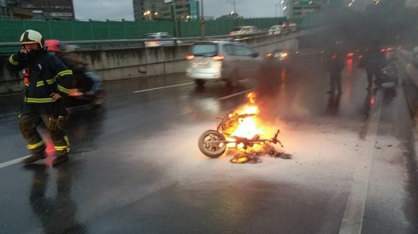 消防局人員據報趕抵,倒地的機車仍在燃燒。(記者陳恩惠翻攝)