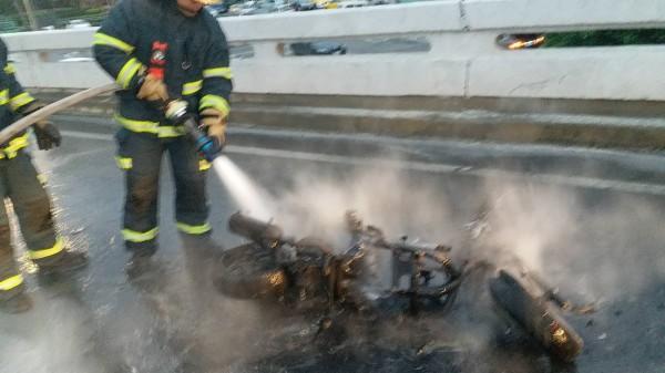 消防救災人員以強力水柱灌救,機車已付之一炬。(記者陳恩惠翻攝)