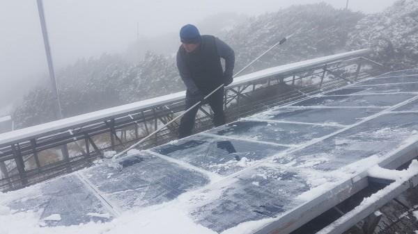 氣象站人員忙著剷雪,確保設備運作正常。(記者劉濱銓翻攝)