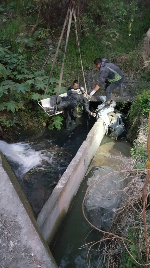 警消將老翁遺體從水溝吊起。(記者張軒哲翻攝)