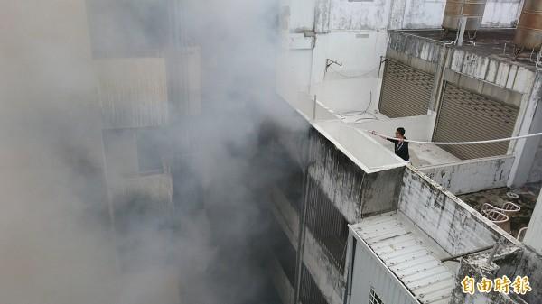 消防人員登上飯店頂樓滅火。(記者陳賢義攝)