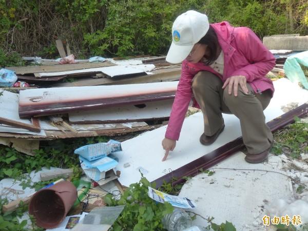 金門環保局科長黃杏玲查察現場的建材廢料留下來源物相關線索。(記者吳正庭攝)