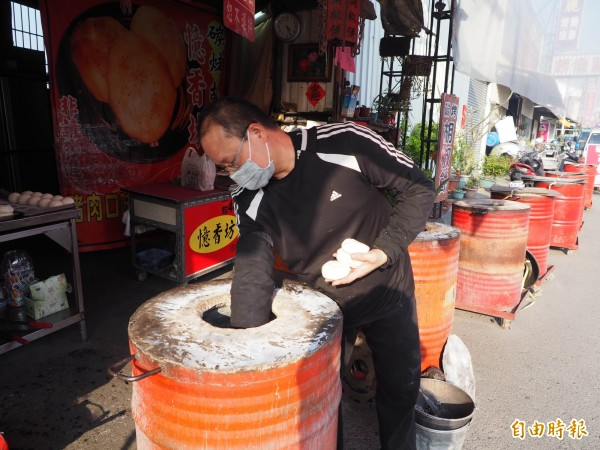 張進義將包好的胡椒餅,一個一個地貼到烤爐內壁上。(記者陳鳳麗攝)