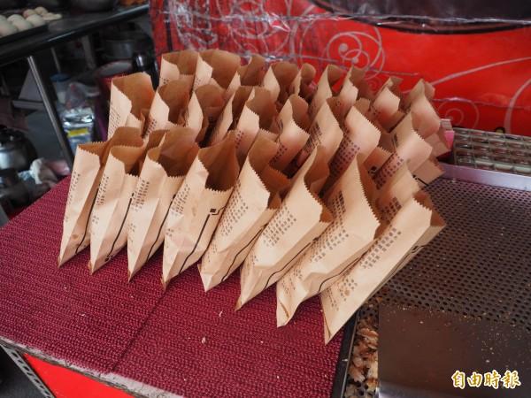 工作人員將胡椒餅一個一個地分裝到紙袋內。(記者陳鳳麗攝)