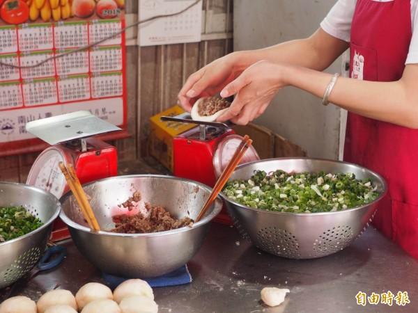 每個胡椒餅放入餡料後都要秤重。(記者陳鳳麗攝)
