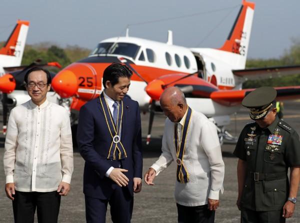 菲律賓國防部長羅倫沙納和日本國防部副部長福田達夫在偵察機交接儀式上互相握手。(歐新社)