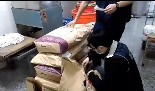 南市調查處人員查扣小叮噹鮮羊乳地下工廠內的牛奶粉與奶精等涉混充羊乳的物證。(記者王俊忠翻攝)