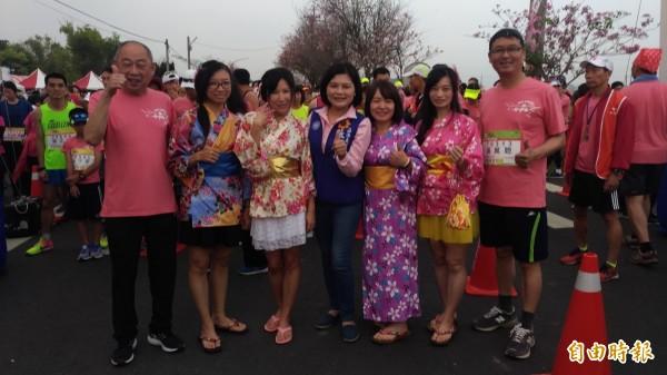 跑友扮成「櫻花妹」和大家合照帶動全場氣氛。(記者廖淑玲攝)