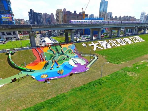 「幸運草地景溜滑梯」園區以七色色塊為園區地面打造繽紛色彩。(新北市政府高灘地工程管理處提供)