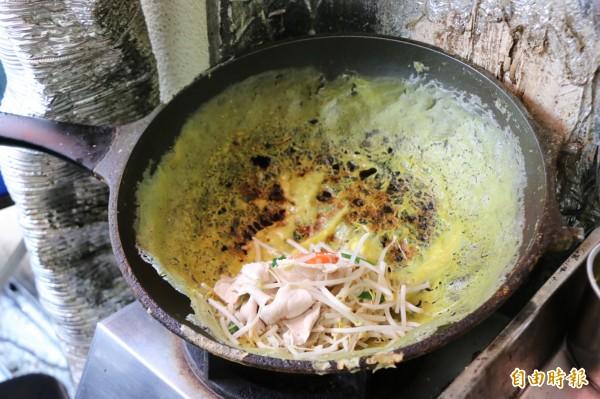 阮秋水以特製的醬汁煎出金黃酥脆的越南蛋餅,再加上肉片、豆芽、蝦子等豐富配料。(記者鄭名翔攝)