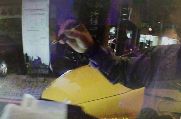 員警密錄器畫面顯示,孫男持筆簽名時用力撇劃,故意將罰單劃破。(記者張瑞楨翻攝)