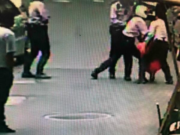 婦人被警方合力制伏。(記者劉慶侯翻攝)