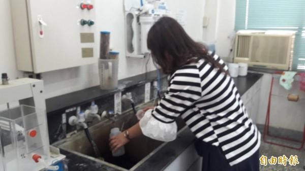自來水公司三區處人員今天到頭前溪隆恩堰取水口取水樣再次檢測,預計2天後有結果。(記者洪美秀攝)
