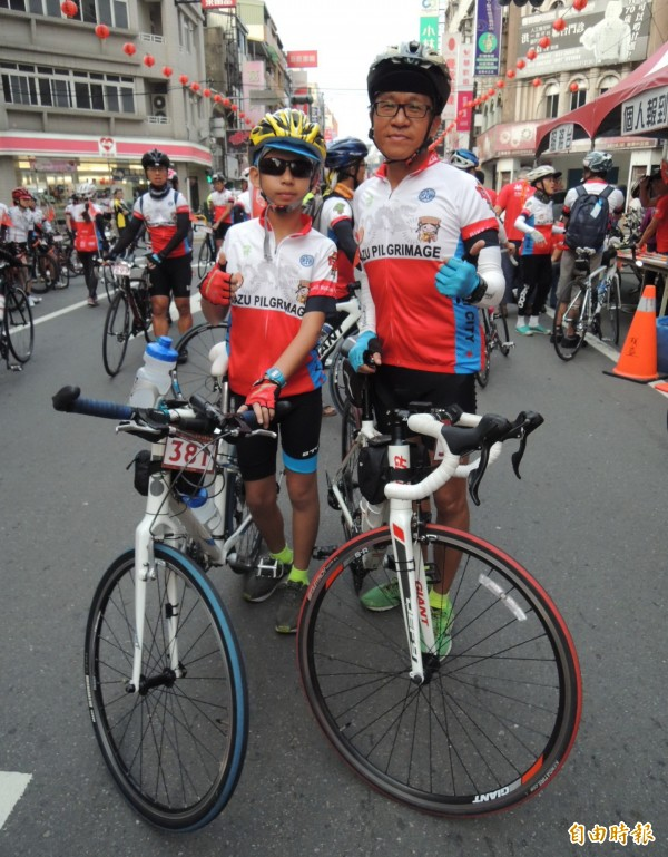 來自台中市12歲的紀冠廷(左),是參與鐵馬進香最年輕的,他由父親紀坤杉陪同首度挑戰300多公里路程。(記者張勳騰攝)