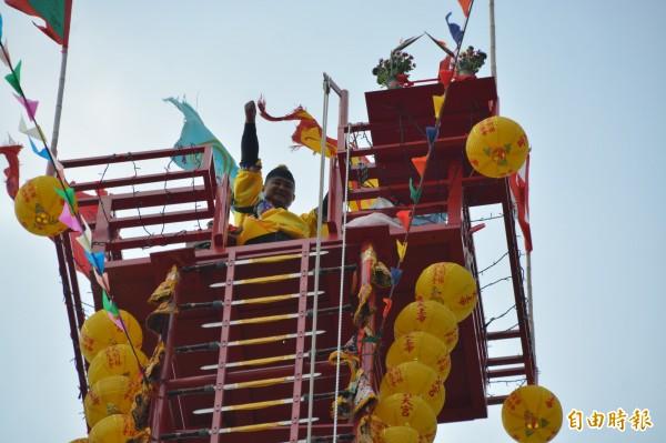 體重約百公斤的道長卓彥男,通過108層刀梯登上天壇後,開心向在下方加油打氣的親友及道友致謝。(記者王峻祺攝)
