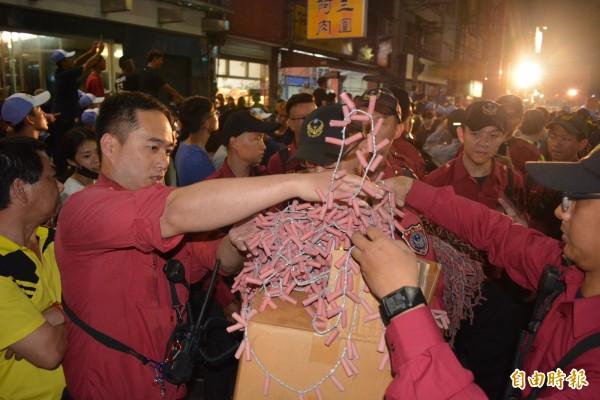消防人員小心翼翼把一串串煙火鞭炮裝入紙箱。(記者張聰秋攝)