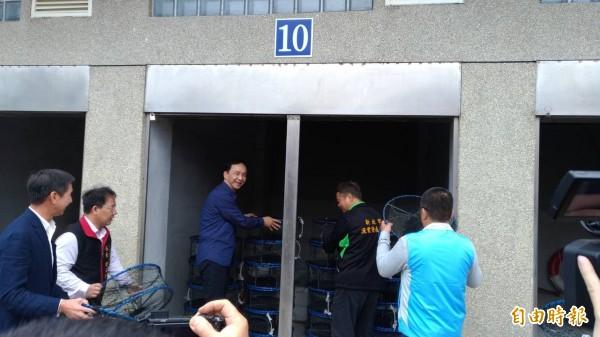 新北市長朱立倫(左三)與漁民一同將捕萬里蟹的籠具,放置嶄新的倉庫內存放。(記者俞肇福攝)