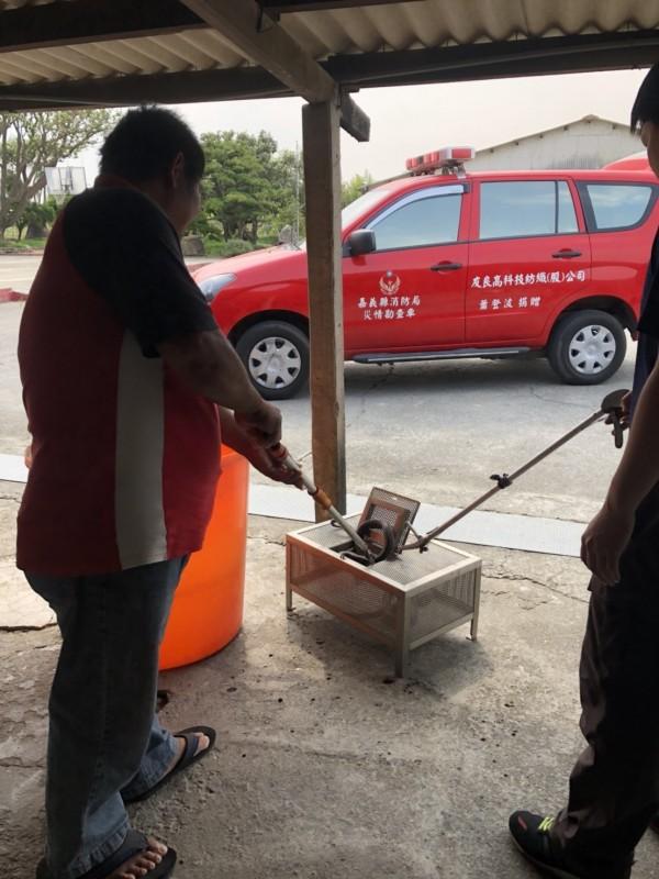 消防隊員逮捕眼鏡蛇,依規定交給相關單位處理。(圖由縣議員戴光宗提供)