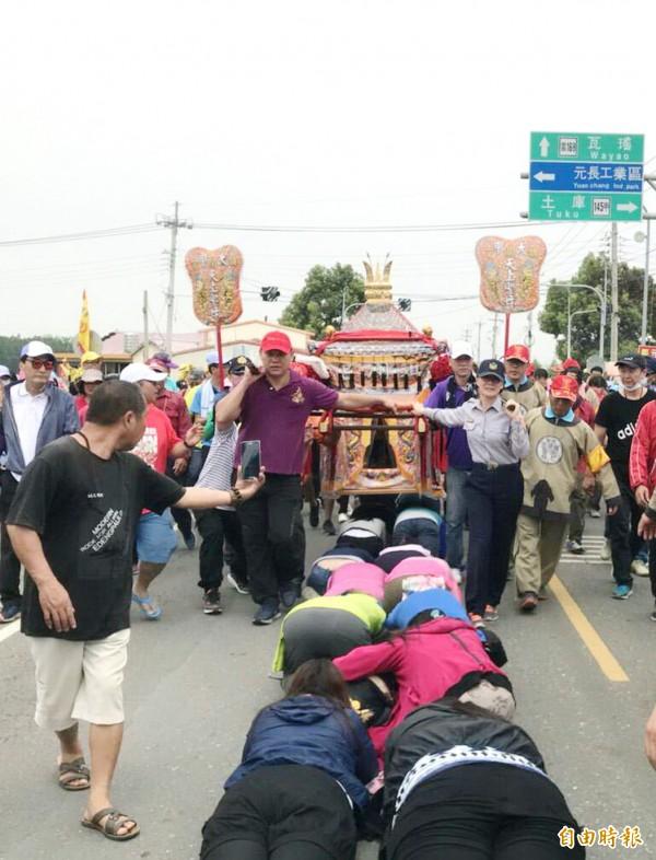 虎尾分局長陳立祺(右抬轎者)首度為媽祖抬轎,沿路信徒列隊「鑽轎腳」。(記者廖淑玲攝)