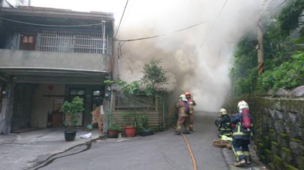 新北市鶯歌中山路一處巷內,今天上午竄出濃煙,消防人員到場,在煙霧瀰漫的屋內尋找火源,搜尋受困住戶。(記者吳仁捷翻攝)