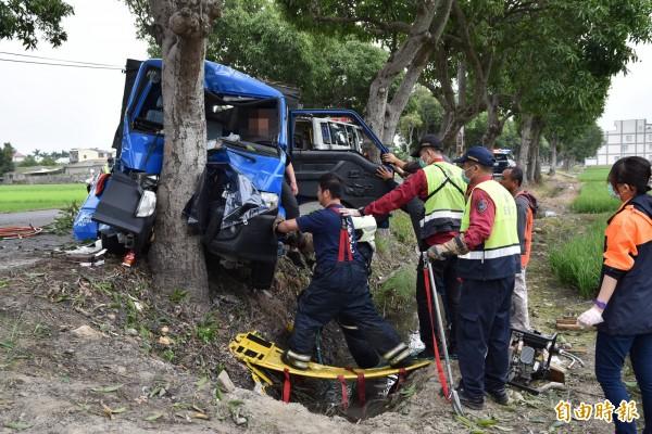 斗南縣道158乙線今天下午發生小貨車撞路樹事故,駕駛受困車內,消防人員以破壞器材搶救。(記者黃淑莉攝)