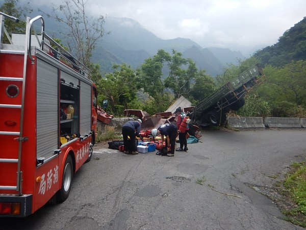 大貨車翻到半個車身翹起,屏縣消防局現場救援。(記者羅欣貞翻攝)