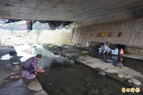 南勢溪仍可見民眾在溪邊洗衣,還有民眾將買來的魚隻拿到溪邊宰殺清洗。(記者歐素美攝)