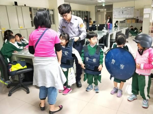 警方讓小朋友體驗試穿警用裝備。(記者鄭名翔翻攝)