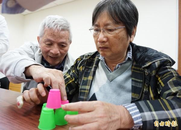 中風的王伯伯與蔡阿姨利用課程所教的疊杯遊戲復健記憶和肢體動作。(記者蔡淑媛攝)