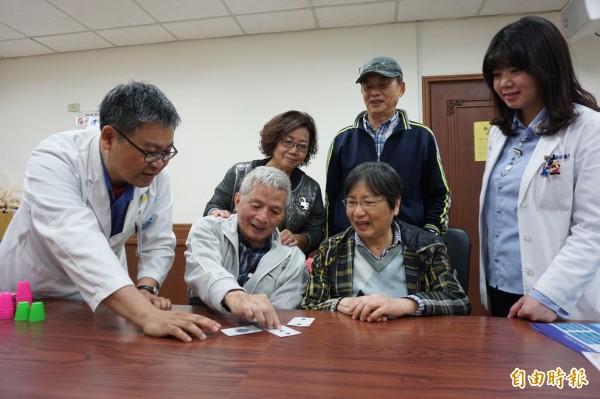 王伯伯與蔡阿姨在家人與職能治療師的鼓勵下利用課程所教的疊杯遊戲復健記憶和肢體動作。(記者蔡淑媛攝)