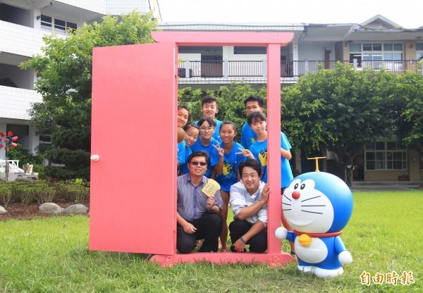 田尾國中校長林正源(左下)、家長會長蕭文勇(右下)為畢業學生打造一座任意門。(記者陳冠備攝)