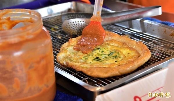 炸好的蔥油餅,沾上老闆特製的甜辣醬,滋味豐富,甜而不膩,為蔥油餅增添不一樣的味道層次。(記者張議晨攝)