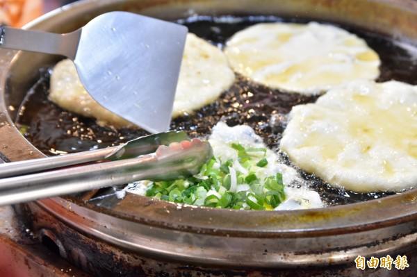 油鍋裡將餅皮雞蛋炸的酥脆,在覆上一把三星蔥,是金珠蔥油餅的一大特色。(記者張議晨攝)