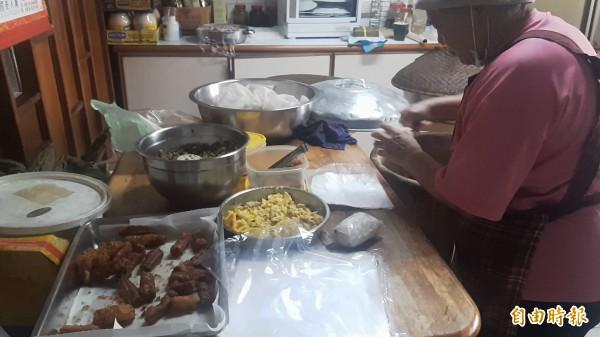 朱家大姊認真包裹飯糰,餡料不假他人之手。(記者陳賢義攝)