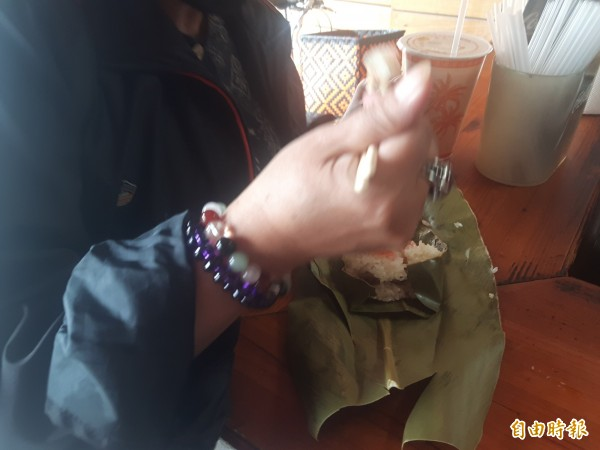 剝開月桃葉,阿拜的香味立馬四溢,食客一口接一口。(記者陳賢義攝)