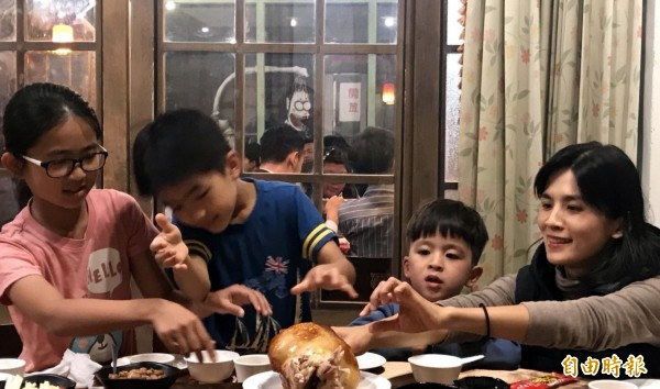 溪頭妖怪村「蝴蝶雞」一上桌,遊客楊筑喨(右)帶著3名孩子,一ロ接一口品嚐。(記者謝介裕攝)