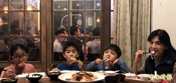 溪頭妖怪村「蝴蝶雞」一上桌,遊客楊筑喨(右)帶著3名孩子,一口接一口品嚐。(記者謝介裕攝)