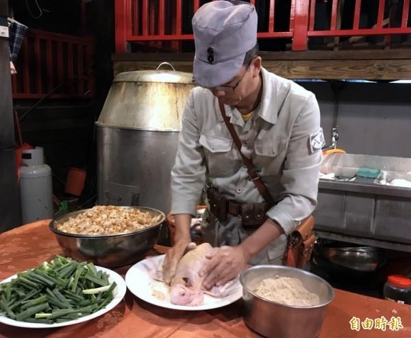 溪頭妖怪村廚師林世昌穿著軍裝工作服,為清洗乾淨的雞隻進行「胡椒浴」情形。(記者謝介裕攝)