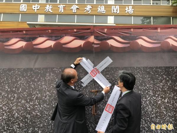 教育部次長林騰蛟(左)及台中市教育局長彭富源(右)為闈場大門上鎖後再貼上封條。(記者歐素美攝)