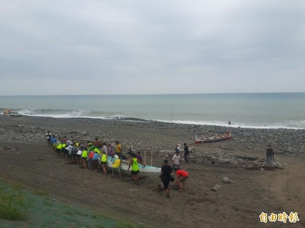 眾人合力將重達500公斤的龍舟拉推到海灘,等待明晨啟航。(記者陳賢義攝)