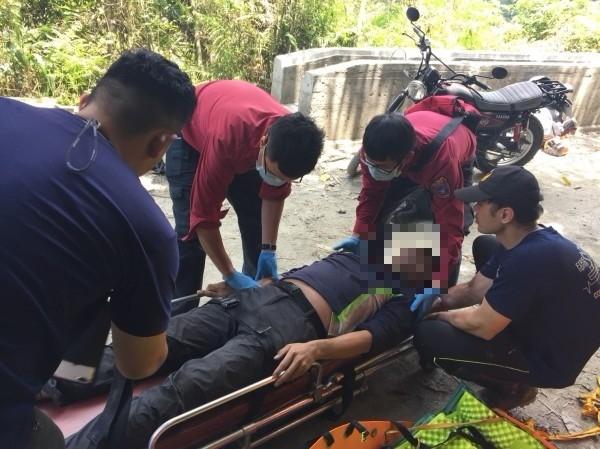 腹部脹大的簡男被移置到擔架上,準備候送醫院,表情十分痛苦。(花蓮縣消防局提供)