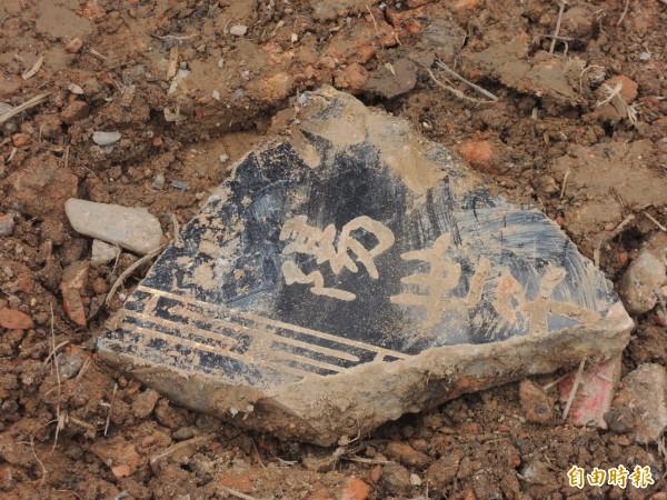 廢棄土方中夾雜墓碑碎片。(記者江志雄攝)