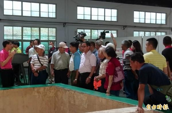 南投縣農會食品廠長吳連俊(左一),向農友說明青梅醃製加工情形。(記者謝介裕攝)