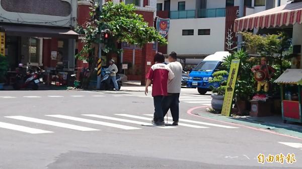 南市安北路1家超商店員工在烈日下陪伴視障朋友等紅綠燈過馬路。(記者洪瑞琴攝)