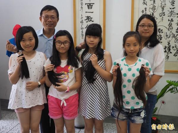 4個發起捐髮助癌友的小女生,其中魏以昕(前排右1)因媽媽林鳳茹(後排右1)曾罹癌掉髮,以昕每次都響應,並陪媽媽一起留頭髮,讓校長陳文燦(後排左1)非常感動。(記者陳鳳麗攝)