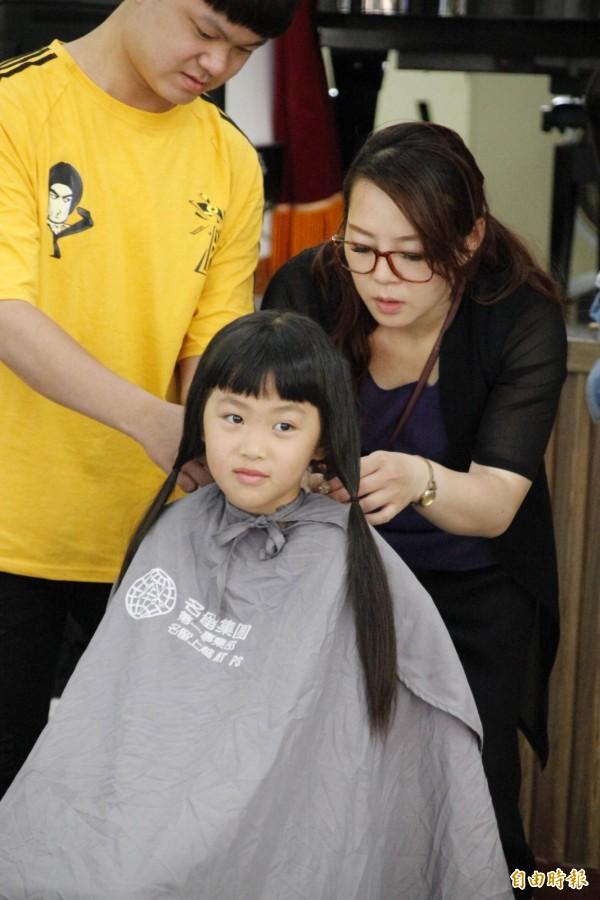 設計師準備幫小朋友剪下要捐的長髮。(記者陳鳳麗攝)