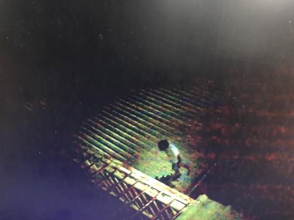 李姓男子爬上鐵皮屋頂,企圖從屋頂逃逸躲藏,最後仍被員警發現,只好乖乖爬下就逮。(記者萬于甄翻攝)